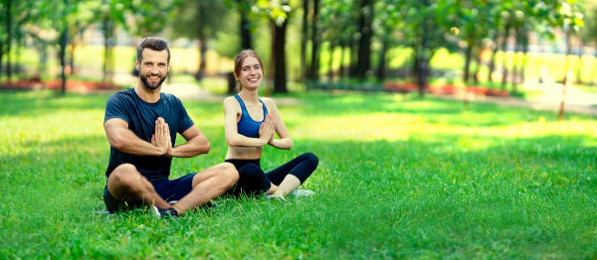 zwei Menschen sitzen in einem Park und meditieren in Kiel.